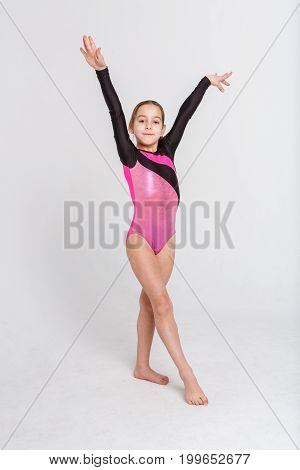 Little girl gymnast in leotard at white studio background. Sporty child in ballet position posing on camera. Healthy and active childhood concept, vertical, copy space