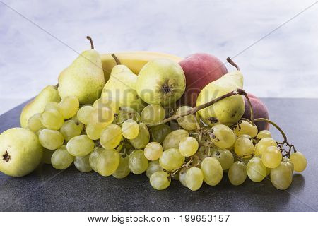 Fruit pears bananas grapes on the kitchen table