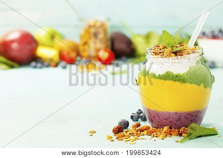 Freshly blended fruit smoothie in glass jar with straw. Turquoise blue background, copy space