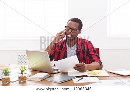 Black businessman discussing documents on cellphone in modern office, copy space