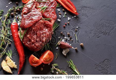Raw rib eye steak with spices and vegetables. Ingredients for restaurant dish. Fresh meat, pepper salt, rosemary, thyme, chilli, tomatoes, garlic, ginger on stone black background with copy space