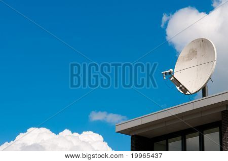 A White Satellite Dish On A Roof