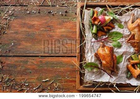 Excuisite restaurant food, copy space. Quails baked to golden crust with asparagus and chanterelles on grungy wooden platter on craft paper. Freshly cooked meals on rustic background, top view