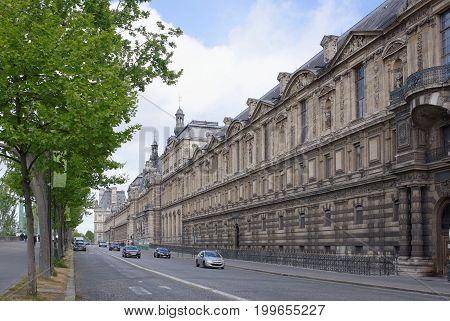 ParisFrance- April 30 2017: Along the waterfront Fransua Miteran past the Louvre moving pedestrians and vehicles