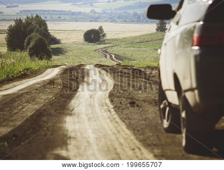 A car next to a winding dirt road that goes into the distance