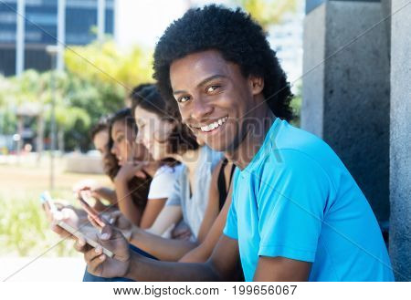 Group of african american man and caucasian and latin woman with cellphone outdoor in the summer