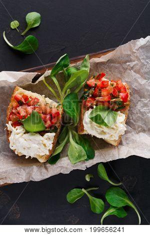 Restaurant appetizer on black background. Crusty bruschetta with concasse tomatoes, stracciatella cheese decorated with spinach. Delicious and healthy meals, top view, copy space, closeup