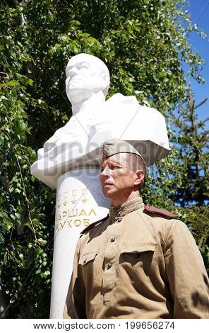 Fighter of Red Army in the form of times of World War II near a bust of the marshal Zhukov with an inscription