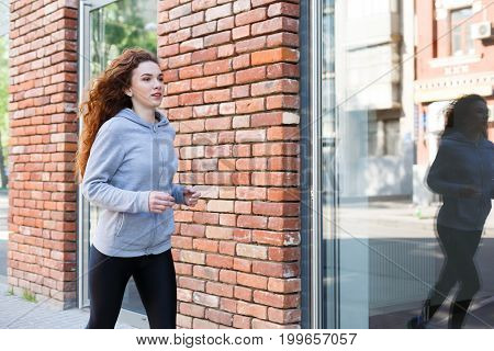 Young redhead woman jogging in city near brick building with mirror windows, copy space