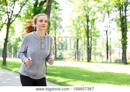 Young sporty woman jogging in green park during morning workout, copy space