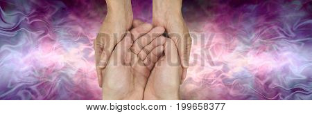 The Beautiful Healing Energy of Carer - female hands gently cradling male hands on a beautiful pink purple flowing energy  background with copy space either side