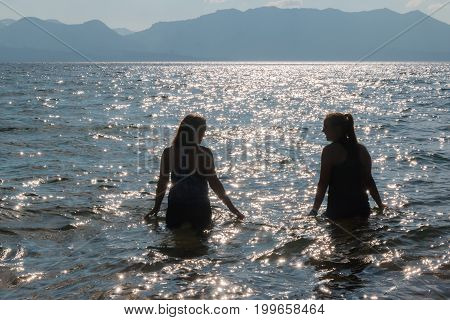 Silhouette Of Two Young Girls In The Water