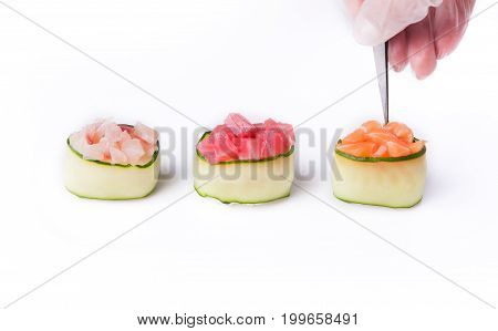 Set of three cucumber gunkans isolated at white background. Chef serving salmon, tuna and seebas sushi. Asian healthy restaurant food delivery