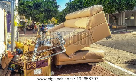 Rishon LeZion Israel-April 16 2016: Residential bulky garbage items are placed on paved sidewalk. There are shabby leather sofa air dryer for laundry and carton boxes full of branches and leaves
