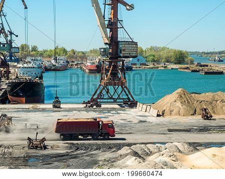 Landscape of tugboats and cranes in shipyard in coast.