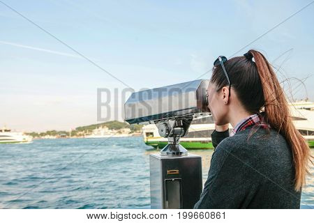 Brunette girl looking at the sea through tourist telescope.