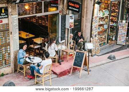 People sitting outside Galata Kofte restaurant in Istanbul, Turkey. A popular place among tourists and local people.