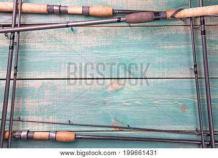Fishing theme. Frame from fishing rods on green wooden background with free space inside