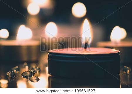 Prayer And Hope Concept - Retro Candle Light In The Church. Vintage Image.