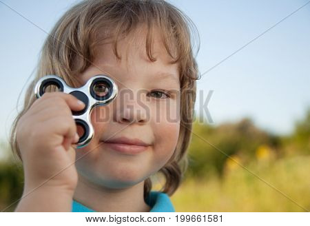 Spinner in the hand of a child smiling in the nature on a summer day.
