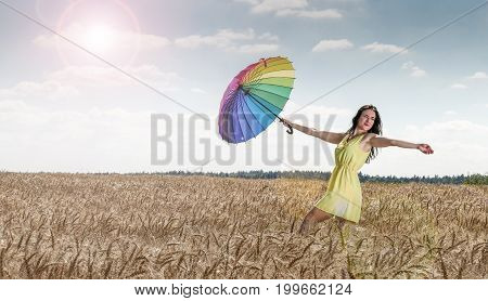 Brunette woman with multy color umbrella in the field.