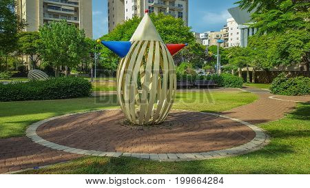 Holon Israel - May 26 2016: Urban sculpture Clown is made with bent painted metal and installed on round cycle in paving stone walkway in small city park. Israeli sculptor Yael Artsi created it.