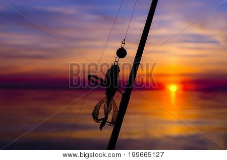 Silhouette Of Fishing Rod With Bait On Sunset Background