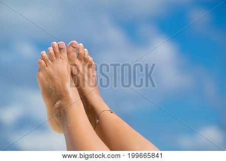 Close-up Of Female Foot In The Blue Sky On The Tropical Beach. Vacation Holidays.