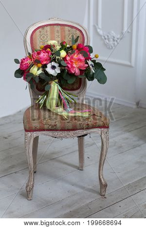 Wedding flowers bouqete on the chair in white studio