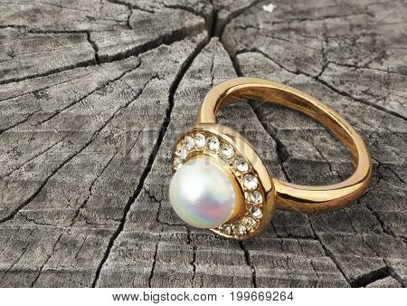 Jewellery ring with pearl on grey wood background