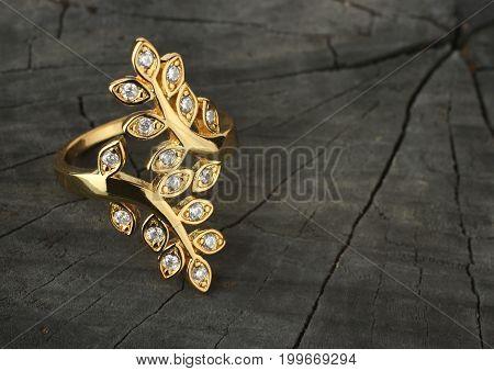 Jewelry ring with diamonds on dark wood background