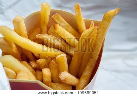 French Fries Potatoes In A Red Paper Bag On A Light Background.