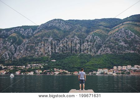 Young tanned man in shorts and a T-shirt is standing on the pier and looking at the sea with mountains in the background. Travel and new impressions. Inspiration.