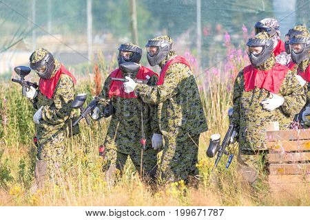 MOSCOW RUSSIA - AUGUST 2017: Paintball sport players in protective uniform and mask preparing for battle