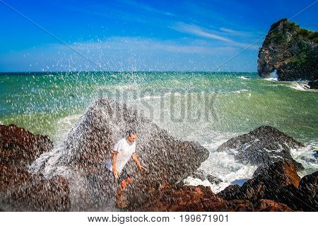 Man escaping incoming big wave on the coast in Thailand