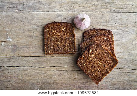 Slices of whole grain brown bread and pungent garlic on wooden table.