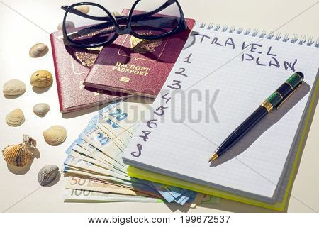 Traveler items on white table. Glasses, passport, euros, Notepad with pen and shell.