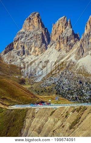Indian summer in the Tirol. Magnificent ridge of dolomite rocks on the Sella Pass, Dolomites. Picturesque road through the pass. The concept of extreme and ecological tourism