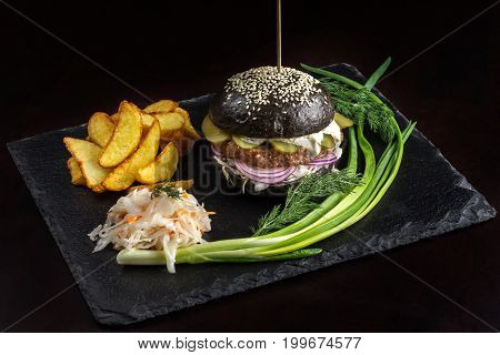 Black hamburger on stone table with black background. Fastfood meal. Delicious Hamburger. Gourmet hamburger.