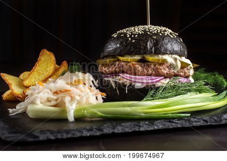 Black hamburger on stone table with black background. Fastfood meal. Delicious Hamburger. Close up.