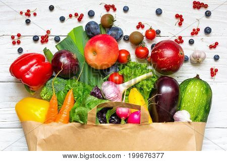 Full paper bag of different fruits vegetables and berries on a white wooden background. healthy food. Top view. Flat lay