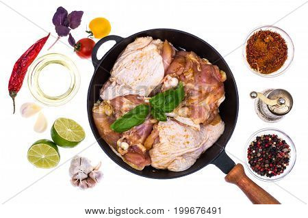Cast-iron frying pan with marinated chicken thighs for frying. Studio Photo