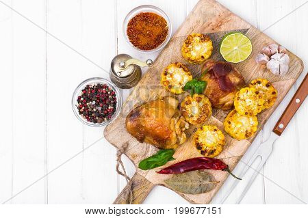 Cajun chicken and corn grilled on wooden board. Studio Photo