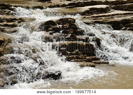 Rapid mountain flow of water over stones