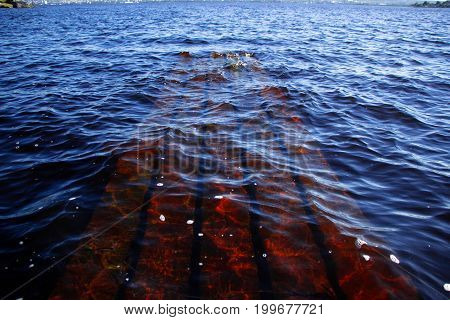 Part of the sunken pier under the clear water of a large lake