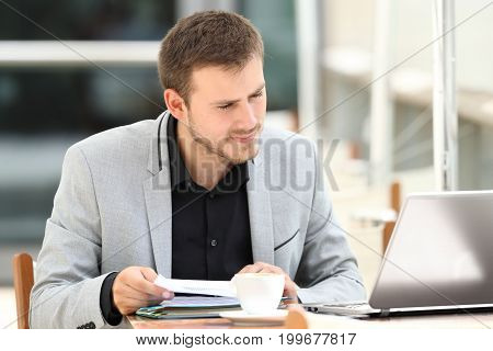 Executive comparing documents on line with a laptop sitting in a coffee shop
