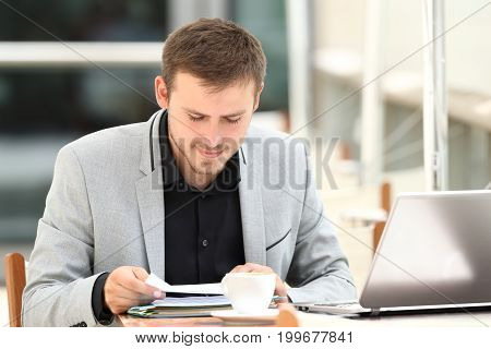 Concentrated executive reading documents sitting in a coffee shop