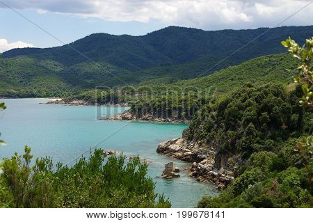 Sea coast near Stagria, Greece. Cliffs covered with lush plants. A blue sky with white clouds can be seen above the azure sea.