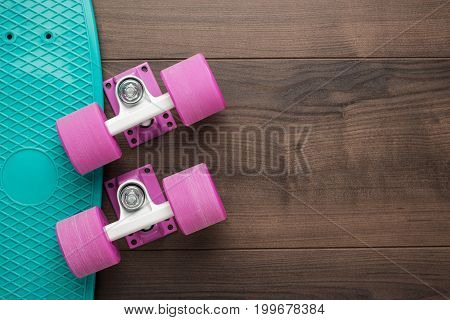 plastic mini cruiser board disassembled on wooden table with copy space