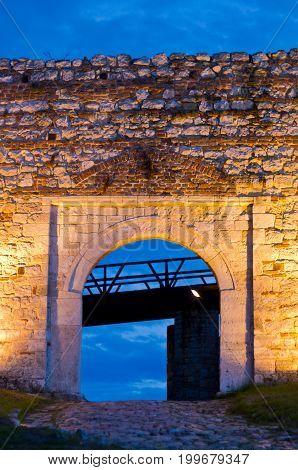 Cobblestone path, fortress gate, and a wooden bridge at twilight  inside Kalemegdan fortress in Belgrade, Serbia